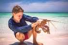 Aidan with caught lobster on the Abrohlos Islands