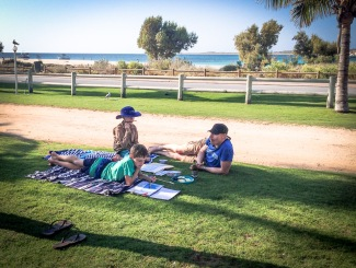boys and geoff doing school work on the grass 3